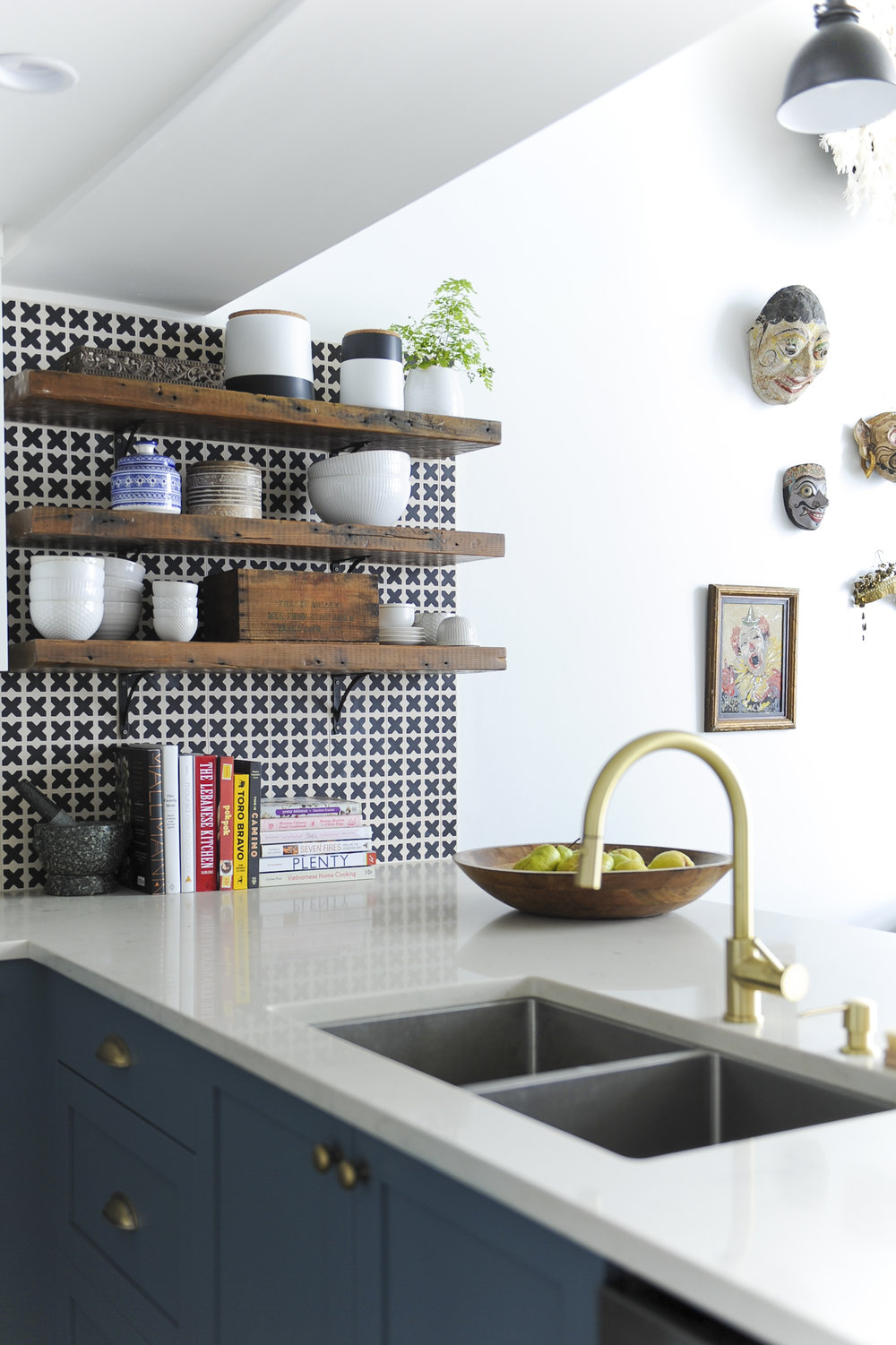 A sunlit kitchen counter and wooden shelves on a black and white patterned tiled wall, complete with various kitchen items, including bowls and ceramic jars on the shelves, and a wooden bowl of fruit and various cookbooks beside a double sink with gold fixtures.