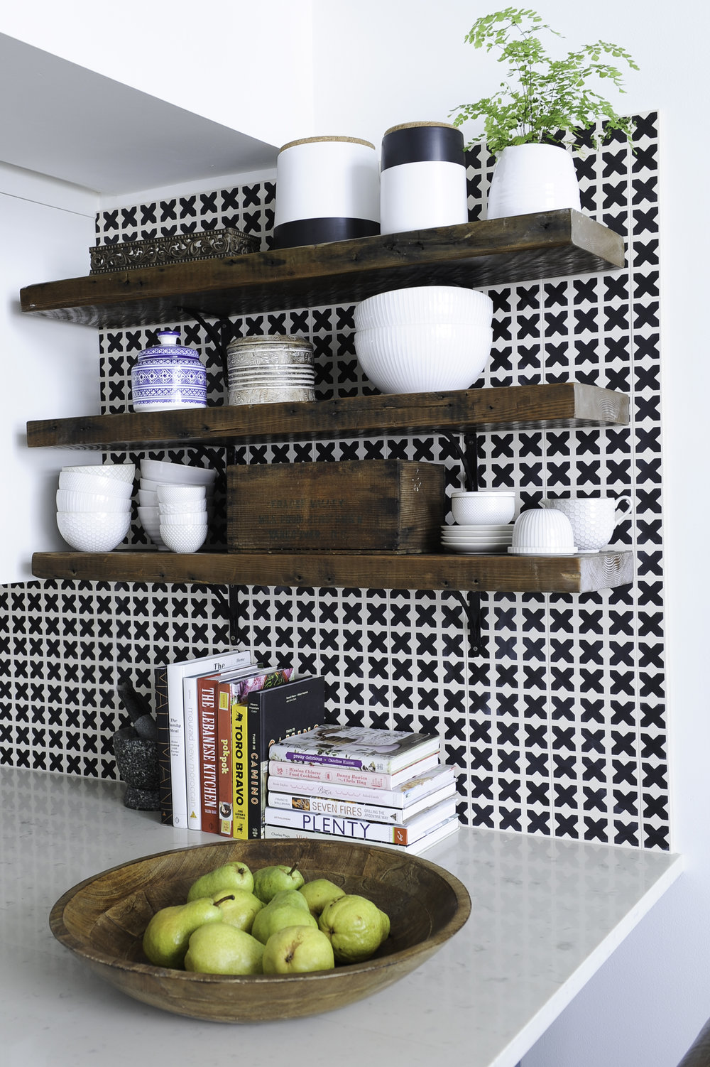 Wooden shelves on a black and white patterned tiled wall, with various kitchen items sat on the shelves, like bowls and ceramic jars and a wooden bowl of fruit and various cookbooks beside a double sink with gold fixtures