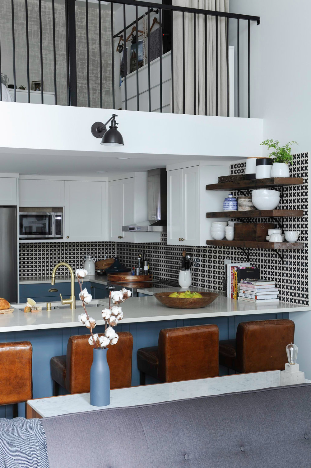 A sunlit kitchen in a loft space, with blue kitchen counters and white countertops, leather bar chairs and a black and white patterned tiled wall.