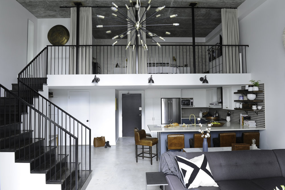 A spacious sunny loft space with white walls and a black staircase leading from the kitchen and living room area up to the bedroom.