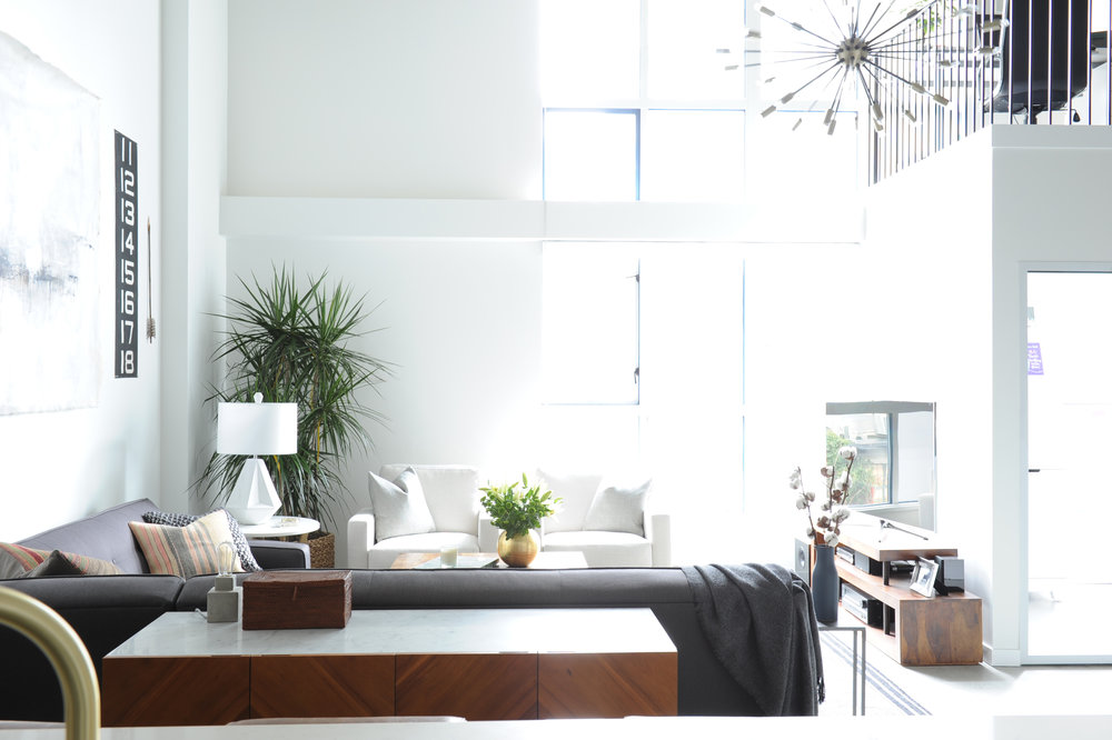 A spacious sunny living room in a loft space with white walls and a home office upstairs