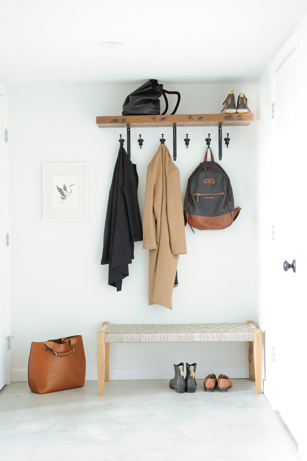 An entrance space that is brightly lit and has a wooden shelf and black hooks with trendy clothes and bags hanging up and shoes under a bench.