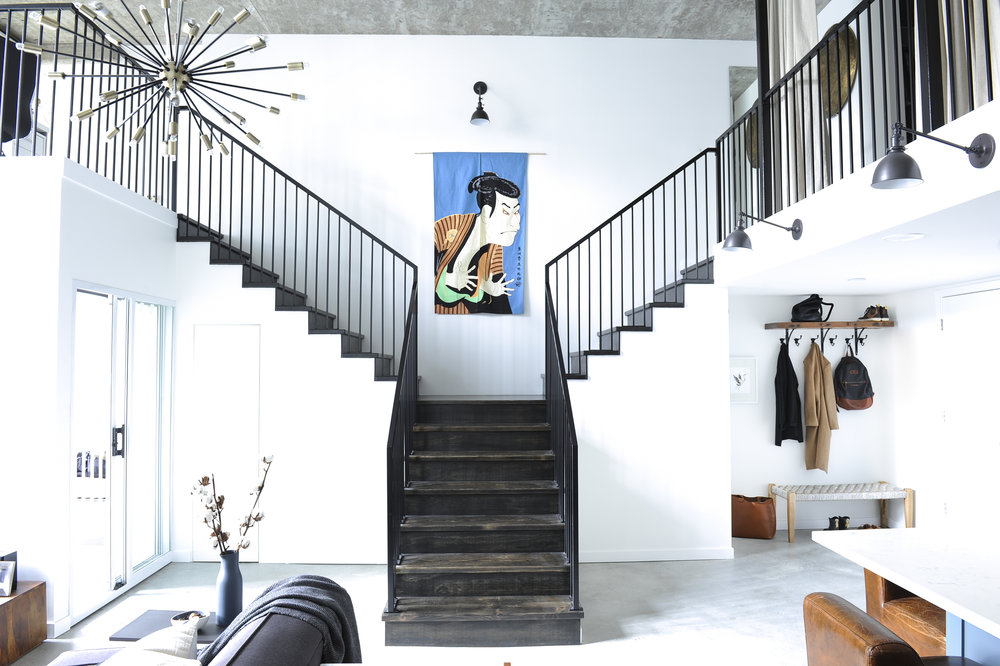 A black staircase in a bright and spacious loft leading up left towards the home office and right towards the bedroom