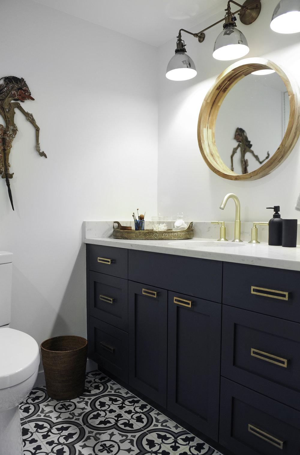 A bathroom featuring a wooden vanity mirror, gold fixtures on the sink and black bathroom cabinets with gold drawer handles.