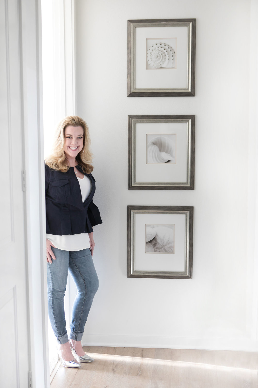 This is a photo of Audra Wrightson, who is an interior designer in Orange County, CA. She is wearing metallic silver shoes and cuffed jeans, standing leisurely by a clean white design with three chrome frames hanging behind her with photos of white beach shells.