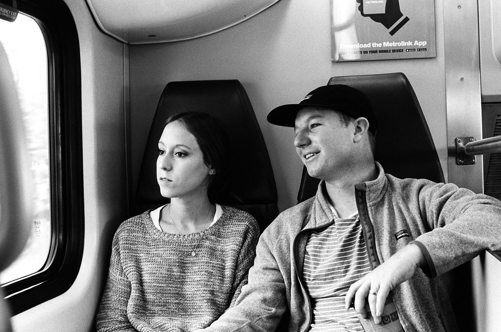 My sister Demi and brother-in-law Austin. En route to LA on Metrolink Orange Line.    Pentax K1000. Kodak Tri-X 400. Fletcher Berryman 2018.