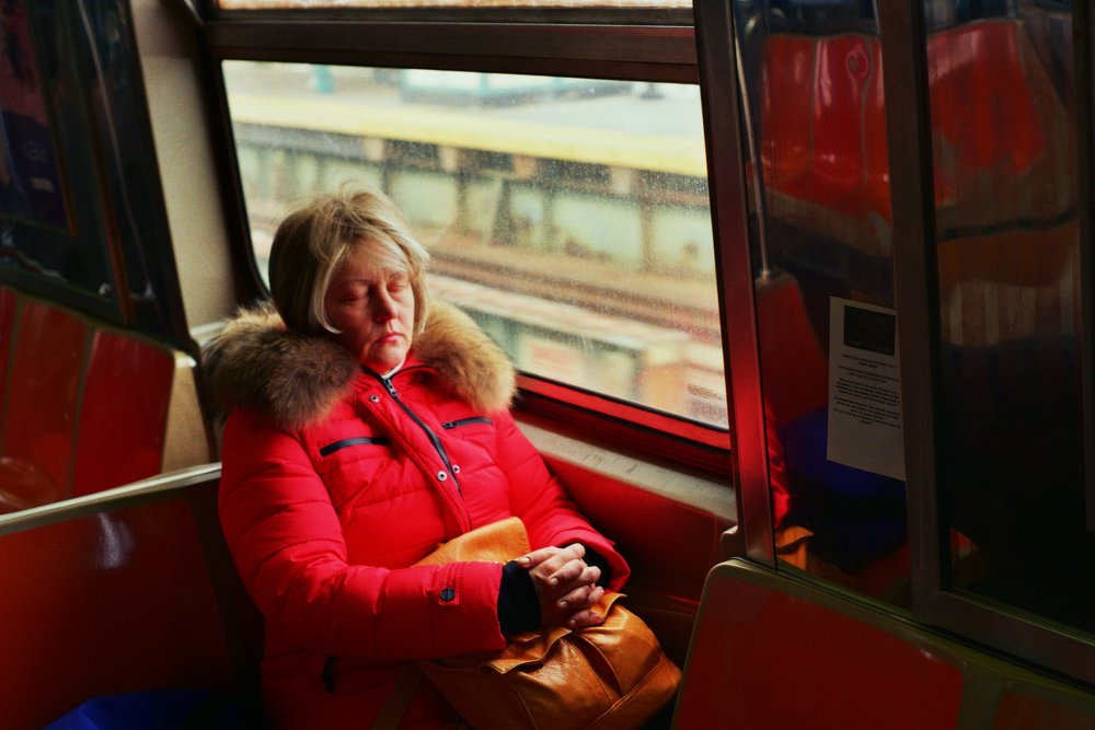 A woman fits in sleep on the southbound D train. Brooklyn, New York.  Kodak Ultra Max 400. Pentax K1000. Fletcher Berryman 2019.