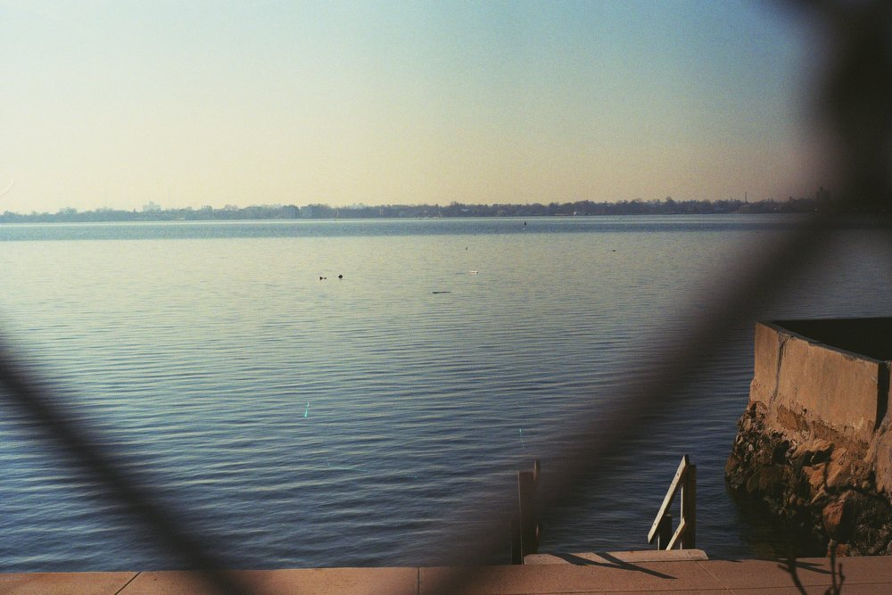 Peeking through the chain-link fench to see what this private beach is all about.  Kodak Ultra Max 400. Pentax K1000. Fletcher Berryman 2019.