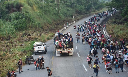 [Photo: Honduran migrants taking part in a caravan heading to the US, walk alongside the road in Huixtla, Chiapas state, Mexico, on 24 October.  Johan Ordonez/AFP/Getty Images ]