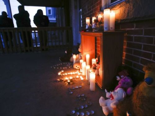 People gather at a makeshift memorial on the porch of a house on the 200 block of N. Broom Street closest to the spot where 16-year-old Jordan Ellerbe was shot and killed in gunfire that wounded two others early Friday evening in January 2015.    [Photo: William Bretzger/The News Journal]