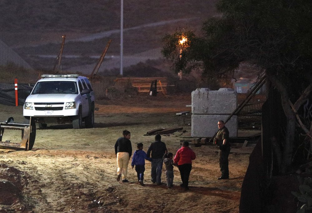 Migrants traveling with children walk up a hill to a waiting U.S. Border Patrol agent just inside San Ysidro, Calif., after climbing over the border wall from Playas de Tijuana, Mexico, Monday, Dec. 3, 2018. Thousands of Central American migrants who traveled with recent caravans want to seek asylum in the United States but face a decision between crossing illegally or waiting months, because the U.S. government only processes a limited number of those cases a day at the San Ysidro border crossing.  [Photo: Rebecca Blackwell/AP]