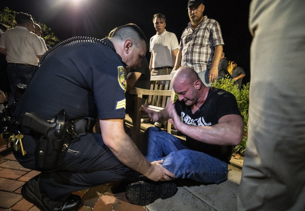 "Christopher Cantwell is helped by police after being overcome by tear gas during the 2017 ""Unite the Right"" rally in Charlottesville. [Evelyn Hockstein/For The Washington Post]"