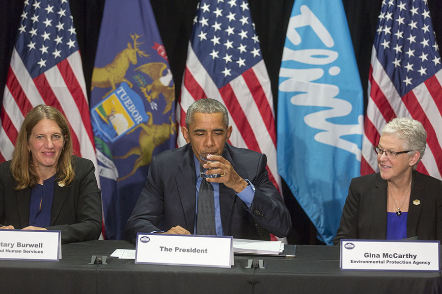 President Barack Obama drinks from a glass of water during a briefing on the Flint public health water crisis during a meeting with federal responders at the Food Bank of Eastern Michigan in Flint, Mich., May 4, 2016. The President is flanked by Health and Human Services Secretary Sylvia Mathews Burwell on the left and Gina McCarthy, Administrator, Environmental Protection Agency.  [Official White House Photo: Lawrence Jackson]