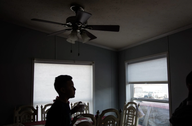 After breakfast at his aunt's house, Isaac Flores Amador, 11, drinks water and listens to a story being told by his extended family.  [Photo: Sebastián Hidalgo for The Washington Post]