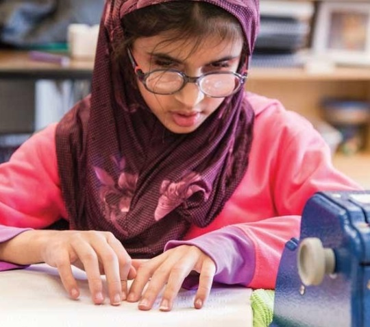 Girl wearing glasses and a hijab, reading braille