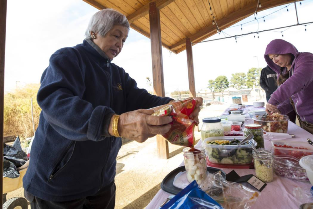 """Leonora Ching, left, author of the """"Pickle-Passion Cookbook,"""" a book on Hawaiian and international recipes, demonstrates her daikon kimchi recipe during a volunteering event at the San Miguel Community Garden located at 3939 Bradley Road in Las Vegas on Saturday, Jan. 12, 2019. Richard Brian Las Vegas Review-Journal @vegasphotograph"""