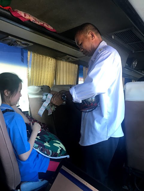 Collecting ticket fare on the bus to Chiang Rai.