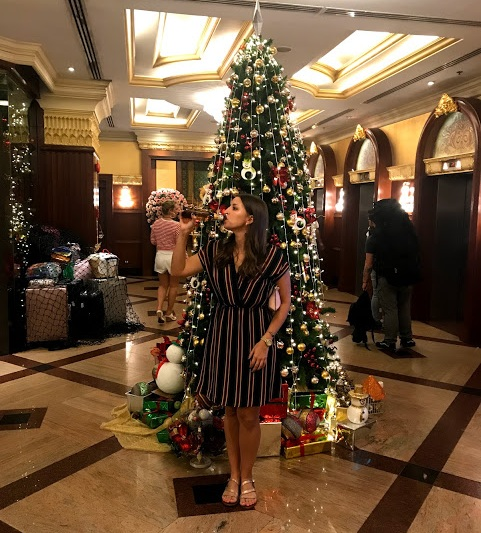 Enjoying an adult beverage in front of the Christmas tree at the Prince Palace hotel!