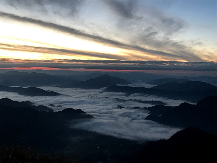 6:35 AM - A streak of coral colored light blazes across the horizon, as the fog blankets the mountain tops.