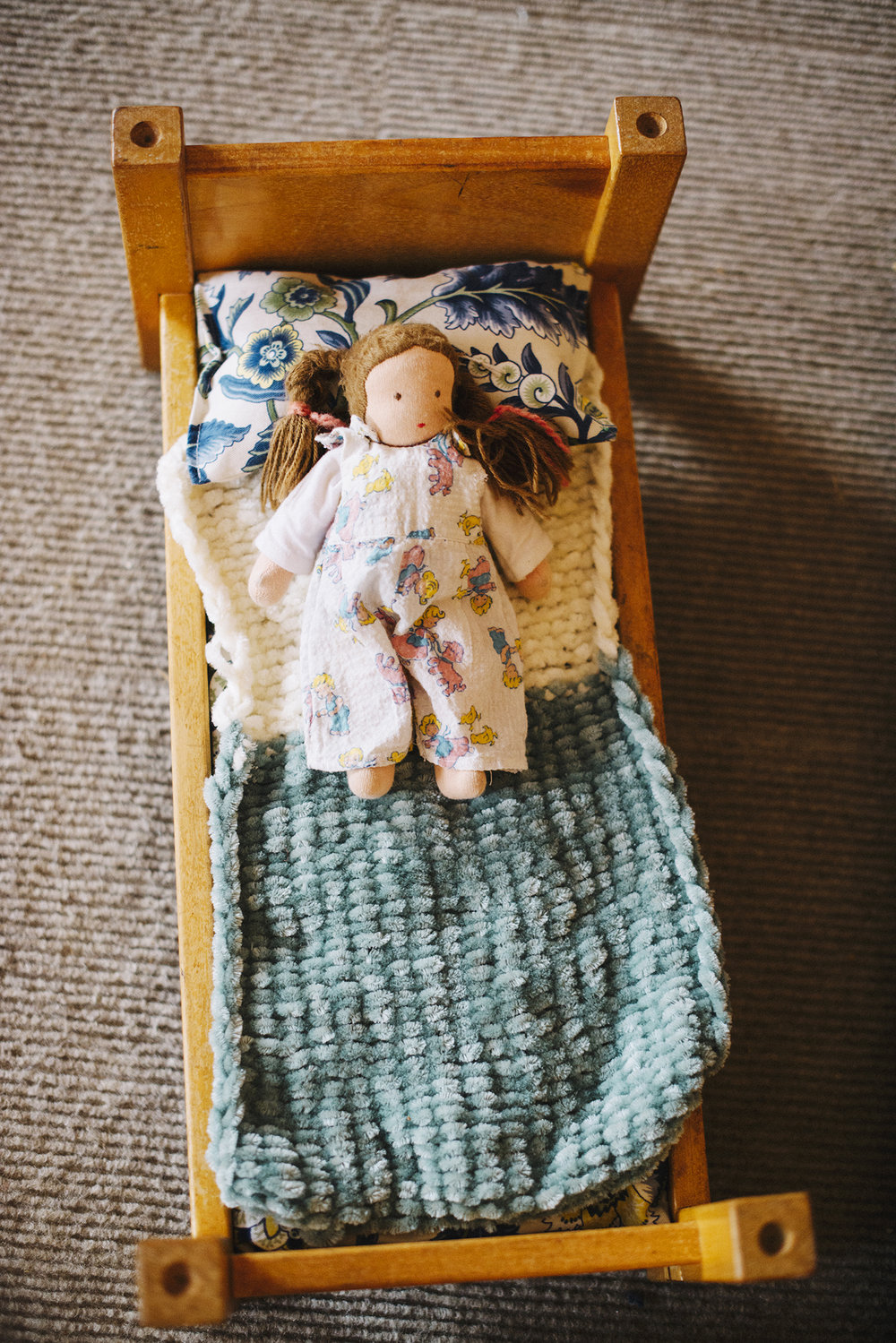 waldorf doll in toy bed.jpg