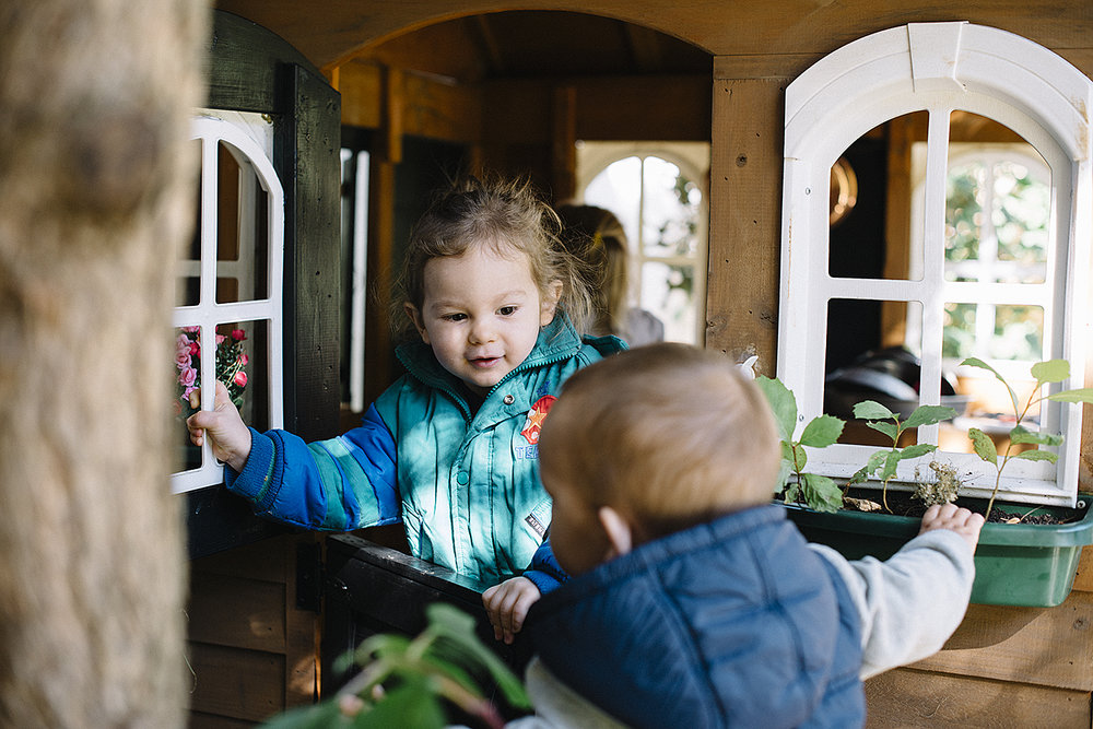 toddlers playing in outdoor playhouse.jpg