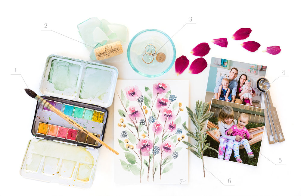 Biographical Flat Lay showing watercolor, wedding rings, wine cork, flower petals, herbs, family photos, and measuring spoons | Sarah Ainsworth Photography