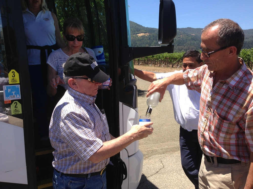 Winemaker Chris Phelps of Swanson Winery pouring a welcome glass as folks get off the bus.
