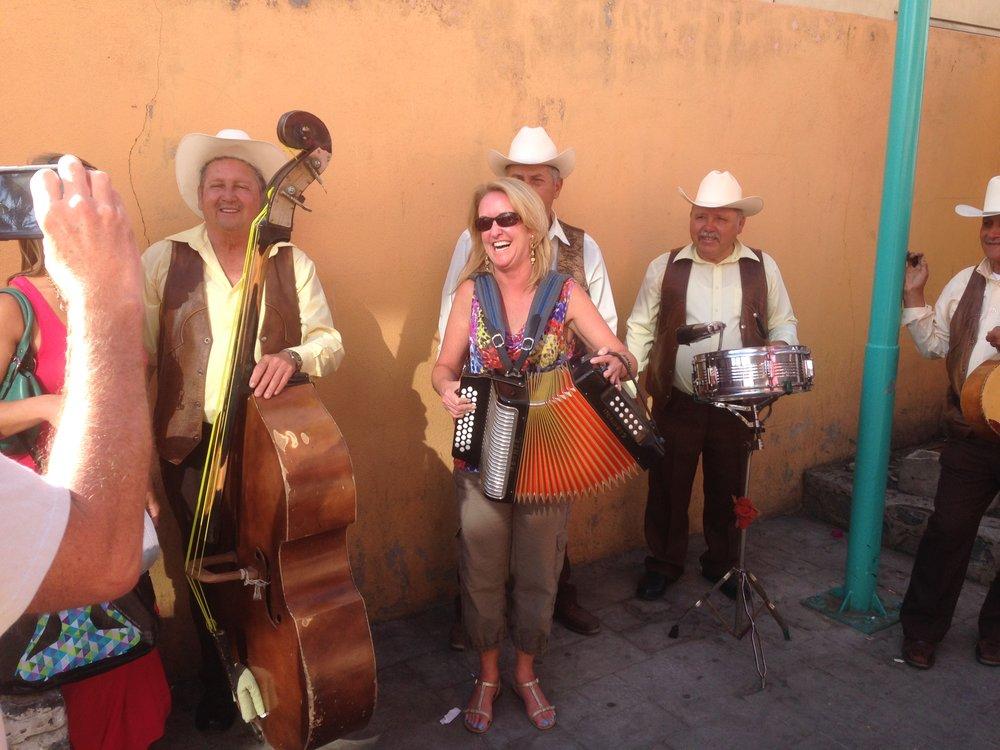 Lynn playing accordian with street musicians in Ensenada