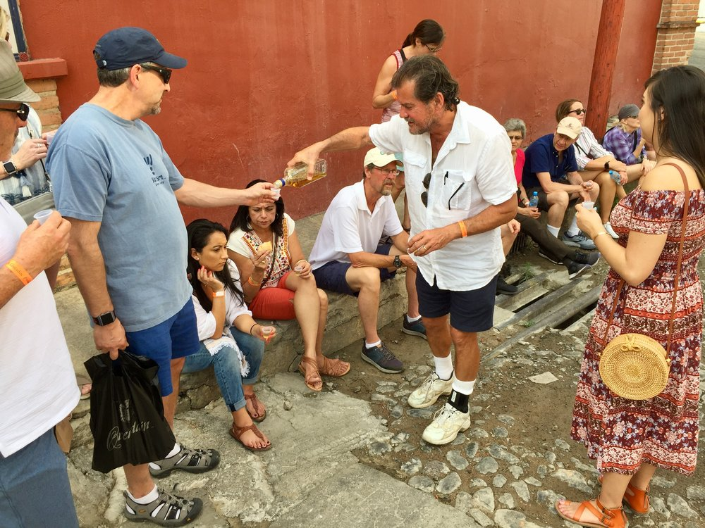 Pouring Arette Tequila on the street in front of El Llano Distillery.