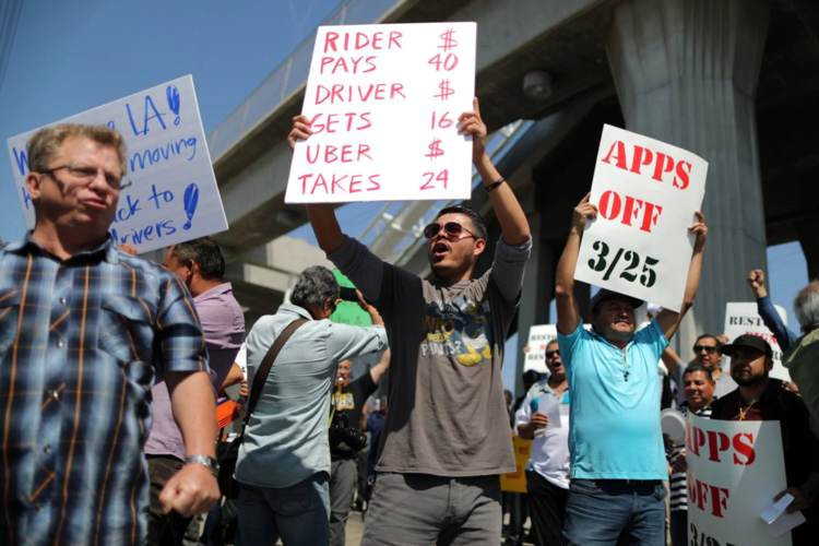 Striking drivers protest Uber's decision to cut per-mile pay to 60 cents from 80 cents, outside an Uber hub in Redondo Beach, Calif. (Lucy Nicholson/Reuters)