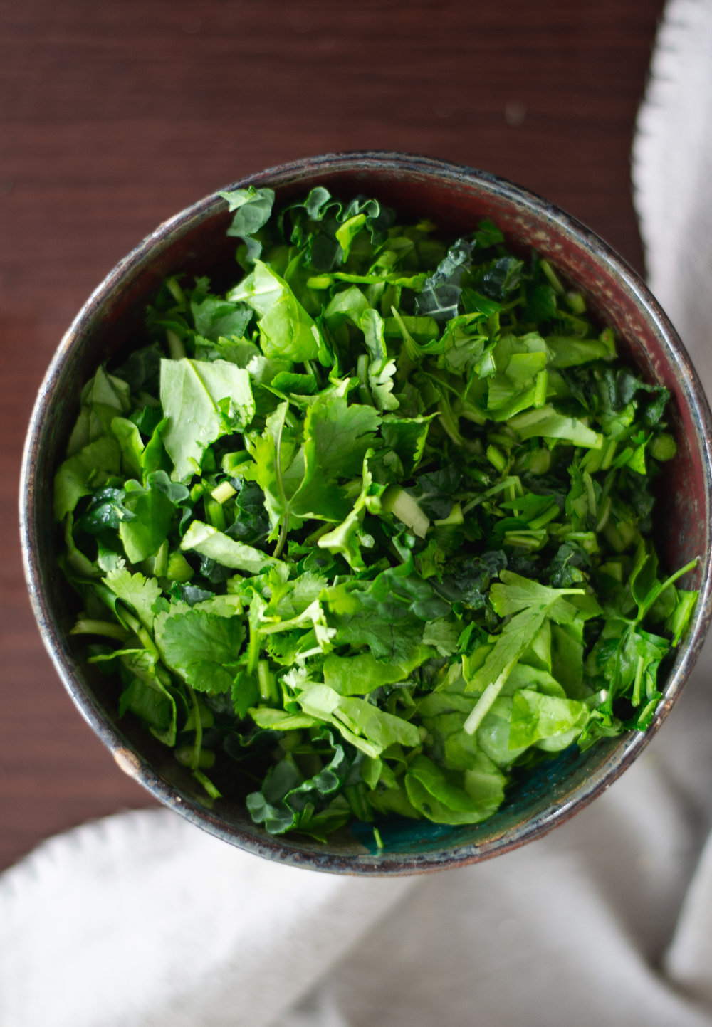 When I'm looking to add more greens to my soup, I will start with a bowl of raw chopped mixed greens (usually kale, spinach, parsley, and cilantro), pour the hot soup over the top, and let the heat gently wilt my greens. Voila a delicious, greens filled soup.  ©Elena Hollenhorst