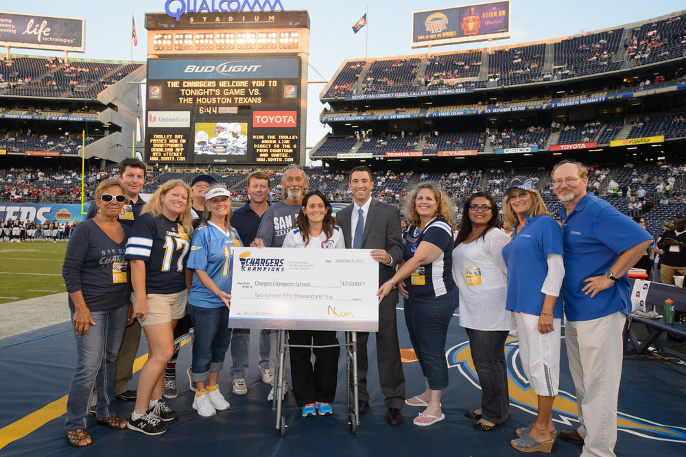 Chargers Champions School Grant Program. Coach Stevens and Coach Maroni from John Muir are on the right in blue.