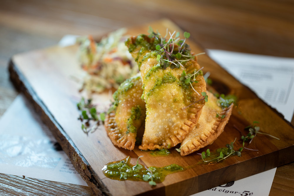 Empanadas - Spanish spiced Kualoa Ranch beef, potatoes, Spanish olives, onions with chimichurri sauce & coleslaw - $11