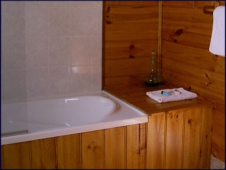 The private ensuite bathroom features a full bath with shower. Self contained bush cabin accommodation at Cradle Mountain Highlanders Cottages in Tasmania Australia with the comforts of home.