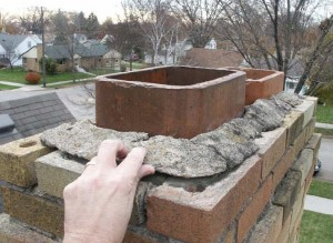 Home inspector demonstrates deteriorated chimney cap and mortar