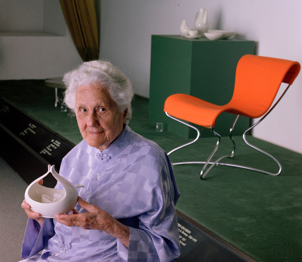 Eva Zeisel at the Museum of Modern Art in 1997, with a piece from a porcelain table service introduced in 1946; behind her is a chair she designed. Credit Fred R. Conrad/The New York Times