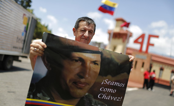 """A supporter of late Venezuela's President Hugo Chavez holds a poster of him outside the Museum of the Revolution in Caracas March 16, 2013. Venezuela's government announced late Friday that the remains of the late Venezuelan President Hugo Chavez would not be embalmed for permanent viewing as originally suggested. The body of Chavez was transferred from the Military Academy to a mountaintop barracks in Venezuela's capital city of Caracas on Friday. The barracks were where Chavez once led an unsuccessful military coup in 1992, and today houses Venezuela's Museum of the Revolution. The words on the poster read: """"Be like Chavez."""" REUTERS/Tomas Bravo (VENEZUELA) - RTR3F3C4"""