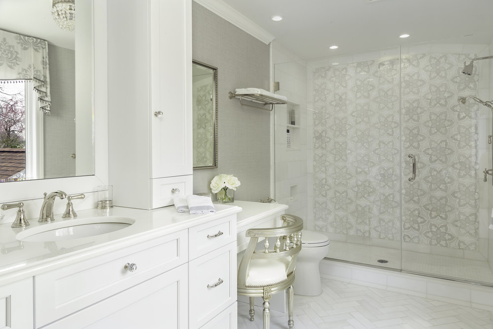 Bright bathroom with tiled shower and white cabinets