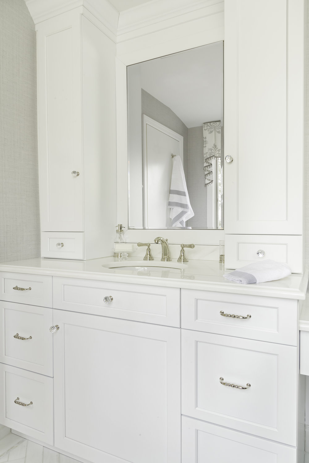 Bright bathroom with white cabinets and mirror over sink