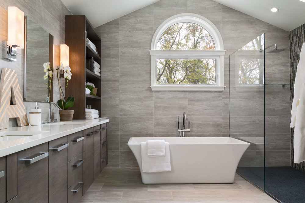Modern bathroom with grey walls and standalone square plunge tub