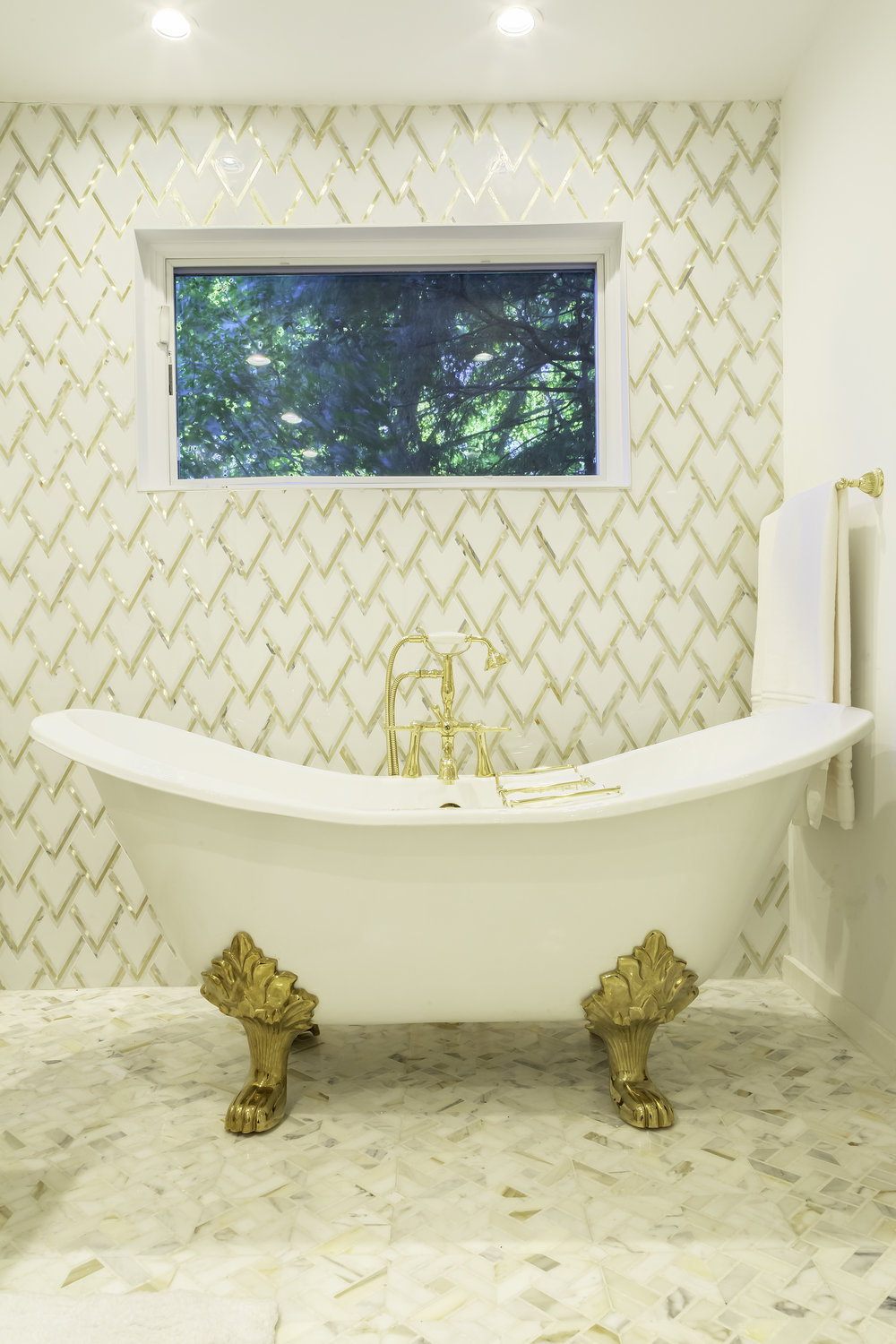 Plunge tub with golden decorative tile on wall behind