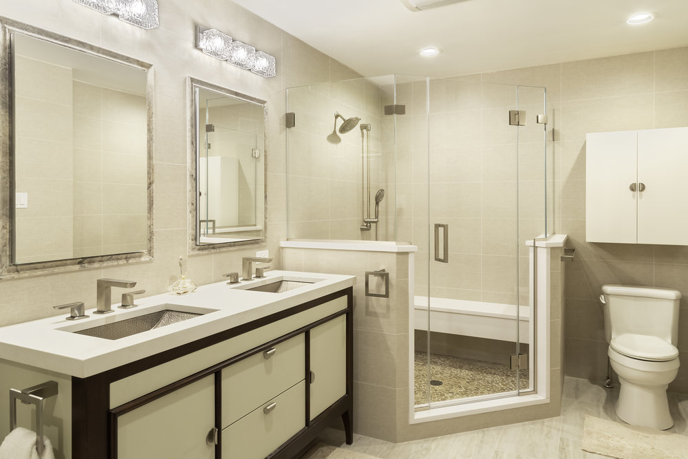 Cream colored bathroom with brown accented sink cabinets