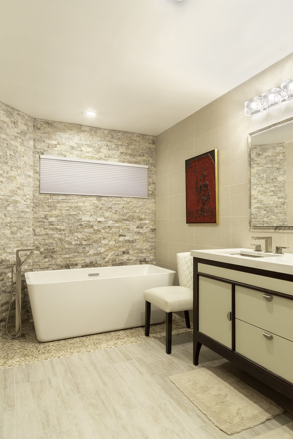 Cream colored bathroom with red painting hanging on wall and plunge bath