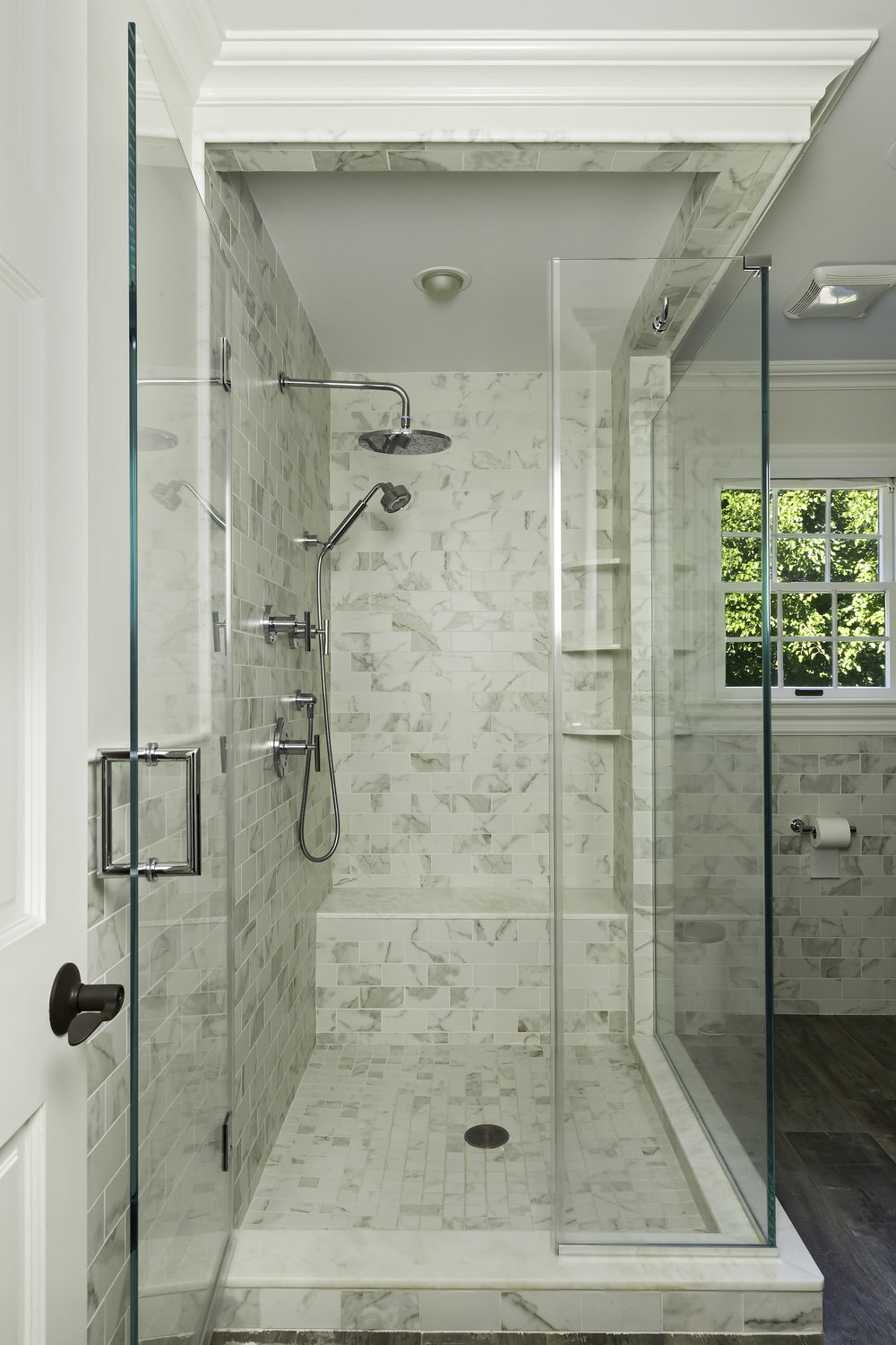 Glass walled shower with multiple shower heads and tiled wall