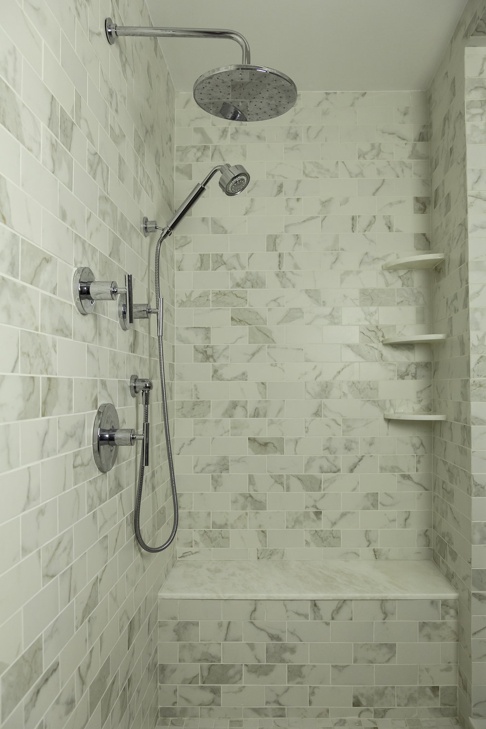 Tile walled standing shower with articulating shower head