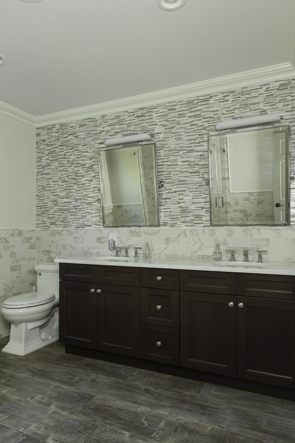 Bathroom with double sinks and angled mirrors hanging above