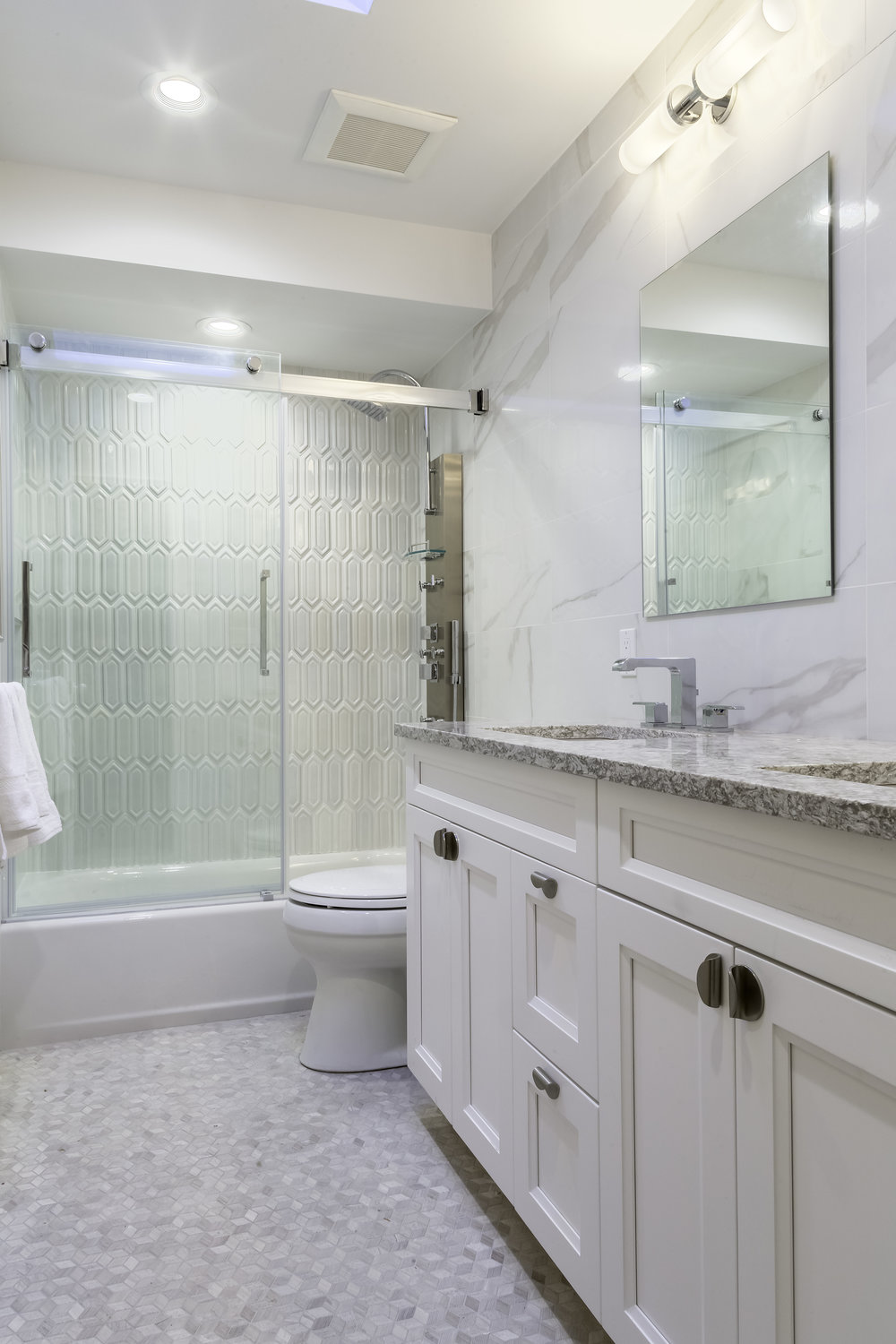 Bright bathroom with marble counter and double sink