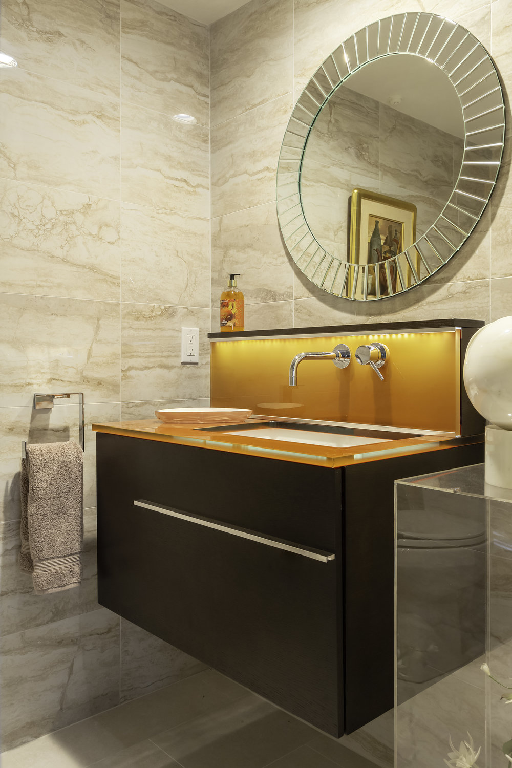 Classic style bathroom with orange surfaced sink and round mirror hanging above
