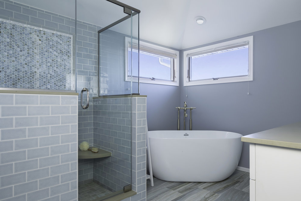 Spacious bathroom with soft blue walls and round plunge bath and separate standing shower