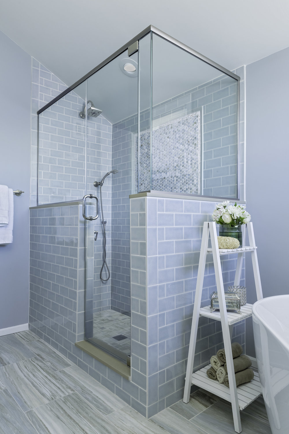 Glass enclosed standing shower with light blue tile walls
